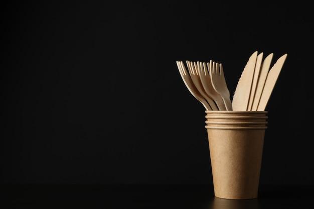 Milieuvriendelijke bekers met vorken en messen op zwart, ruimte voor tekst