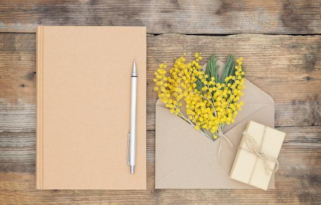 Milieuvriendelijke compositie met de envelop van de giftdoos van de notitieboekjeppen en boeket van mimosa