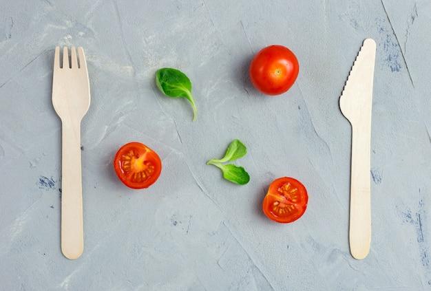 Milieuvriendelijke houten mes en vork op grijs