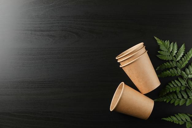 Milieuvriendelijke kopjes en plant op zwart, ruimte voor tekst