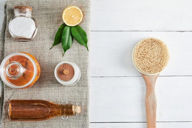 Milieuvriendelijke natuurlijke reinigingsmiddelen zuiveringszout, zeep, azijn, zout, koffie, citroen en penseel op houten tafel. geen afvalconcept.