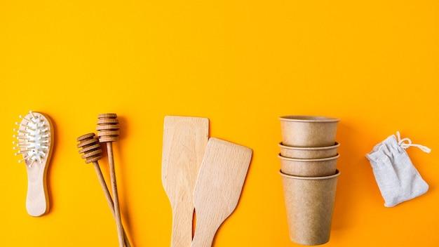 Milieuvriendelijke papieren wegwerpbekers, houten keukengerei, haarborstel en katoenen tas