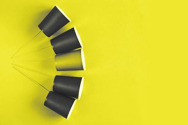 Milieuvriendelijke papieren wegwerpbekers op gele achtergrond