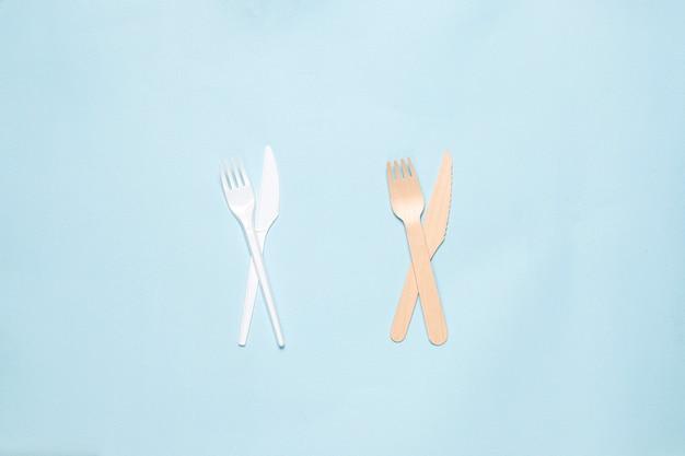 Milieuvriendelijke wegwerp gebruiksvoorwerpen gemaakt van bamboe hout en papier op een blauwe achtergrond. gedrapeerde lepels, vork, messen, bamboe kommen met papieren bekers.