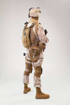 Militair in de marine van de vs eenvormig met geweer op lichtgrijze achtergrond, studioschot