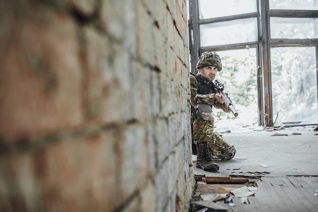 Militair in de vorm houdt in de handen van een groot geweer, lijkt op tegenstanders uit de hoek.
