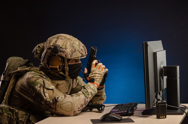 Militair in uniform zittend achter de computer leidt de cyberoorlogvoering met een pistool op de monitor