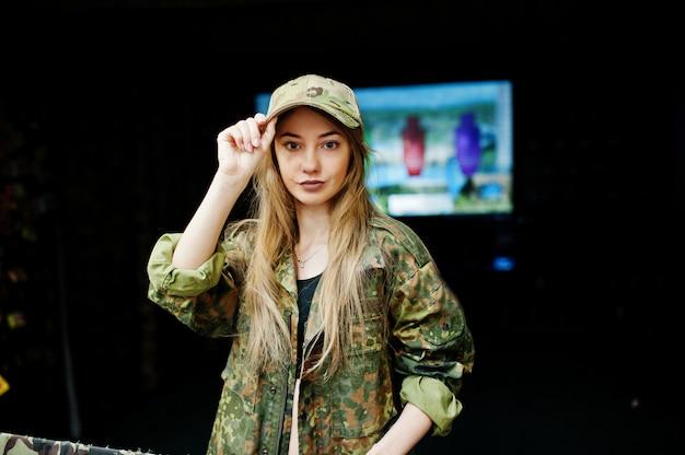 Militair meisje in camouflage eenvormig tegen legerachtergrond op schietbaan.
