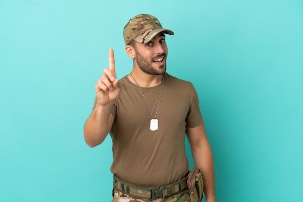 Militair met dog tag over geïsoleerd op blauwe achtergrond die een vinger toont en opheft