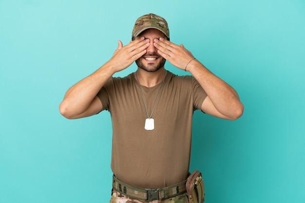 Militair met dog tag over geïsoleerd op blauwe achtergrond die ogen bedekt door handen