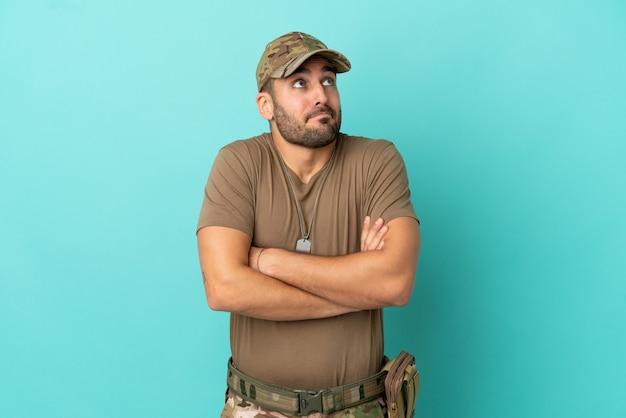 Militair met dog tag over geïsoleerd op blauwe achtergrond die twijfels gebaar maakt terwijl hij de schouders opheft