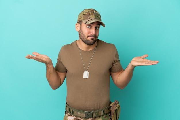 Militair met dog tag over geïsoleerd op blauwe achtergrond die twijfels heeft terwijl hij zijn handen opsteekt