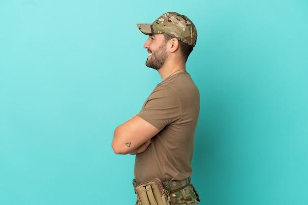 Militair met dog tag over geïsoleerd op blauwe achtergrond in zijpositie