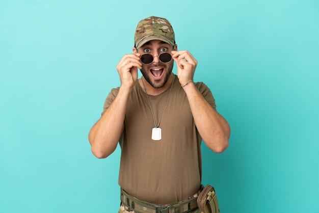 Militair met dog tag over geïsoleerd op blauwe achtergrond met een bril en verrast