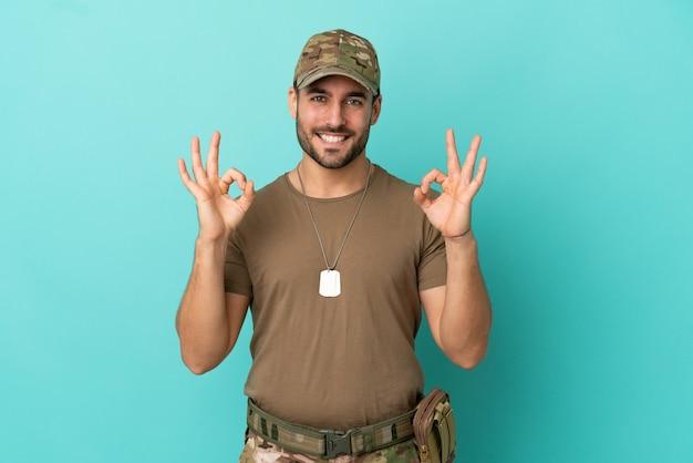 Militair met dog tag over geïsoleerd op blauwe achtergrond met een ok teken met vingers