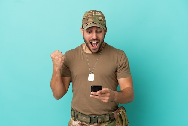 Militair met dog tag over geïsoleerd op blauwe achtergrond verrast en het verzenden van een bericht