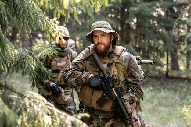 Militaire leider die door de richtkijker kijkt en zijn team voorbereidt op de aanval