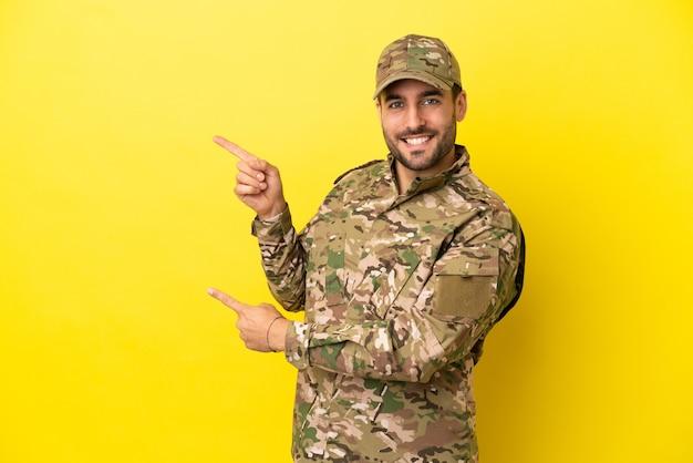 Militaire man geïsoleerd op een gele achtergrond die met de vinger naar de zijkant wijst en een product presenteert