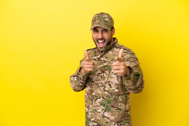 Militaire man geïsoleerd op een gele achtergrond die naar voren wijst en glimlacht