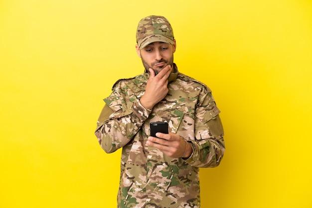 Militaire man geïsoleerd op gele achtergrond denken en een bericht verzenden