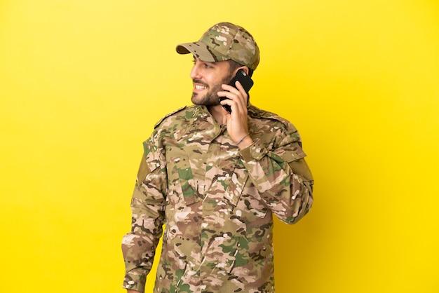 Militaire man geïsoleerd op gele achtergrond die een gesprek voert met de mobiele telefoon met iemand