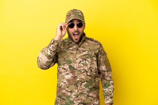 Militaire man geïsoleerd op gele achtergrond met een bril en verrast
