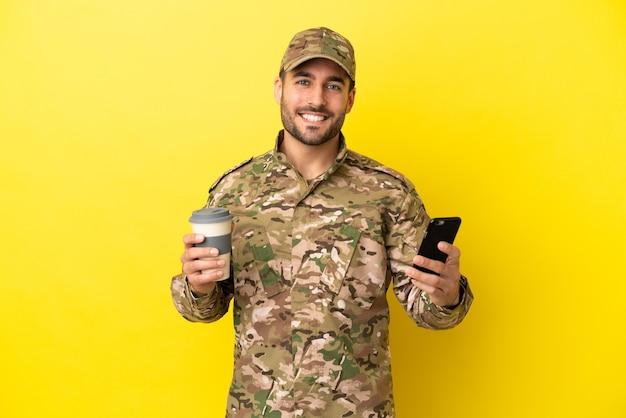 Militaire man geïsoleerd op gele achtergrond met koffie om mee te nemen en een mobiel