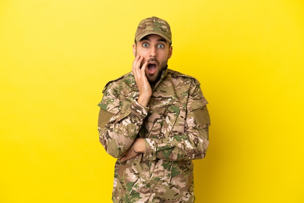 Militaire man geïsoleerd op gele achtergrond verrast en geschokt terwijl hij naar rechts kijkt