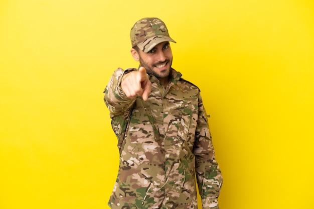 Militaire man geïsoleerd op gele achtergrond wijst vinger naar je met een zelfverzekerde uitdrukking