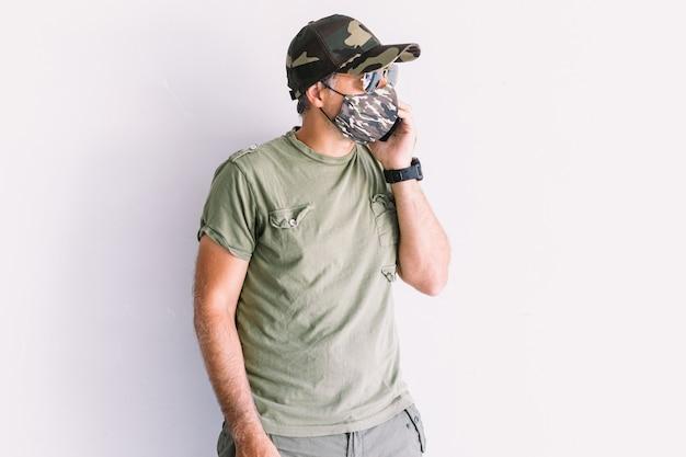 Militaire man gekleed in camouflagepet, zonnebril en camouflagemasker, pratend op de mobiele telefoon, op een witte muur