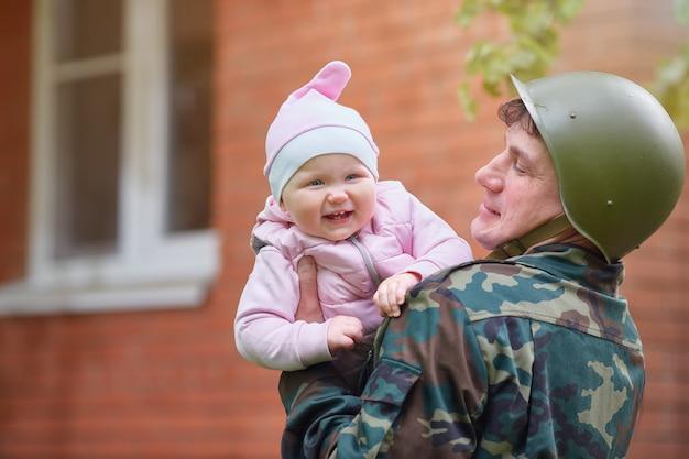 Militaire man in een helm met een lachende kleine baby in zijn armen
