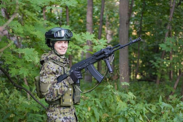 Militaire man in het bos met een machinegeweer. het leger trainen voor de strijd.