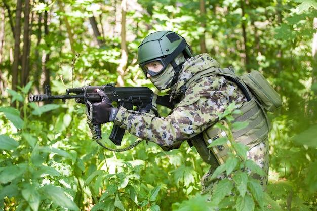 Militaire man in het bos met een machinegeweer. het leger voorbereiden op vijandelijkheden. het machinegeweer mikt