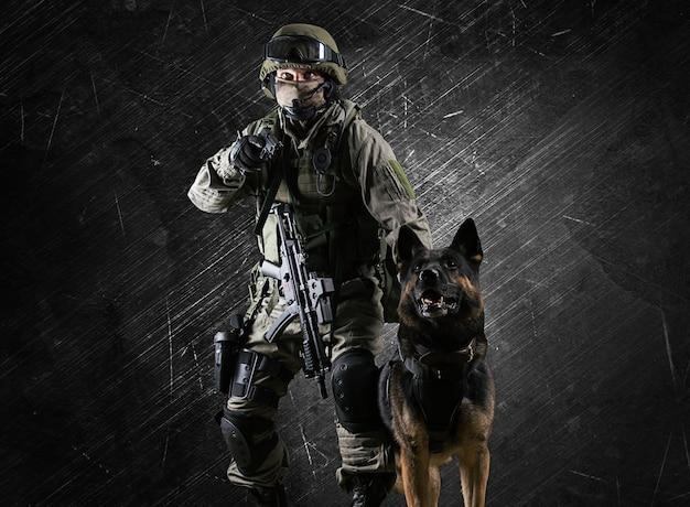 Militaire man in uniform met een wapen in zijn handen zet de herdershond op een crimineel. gemengde media