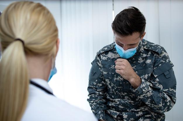 Militaire man in uniform met gezichtsmasker hoesten bij artsen kantoor