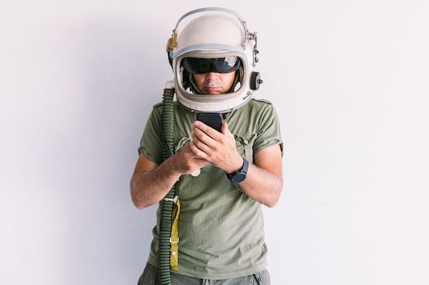 Militaire man met astronaut kosmonaut helm, kijkend naar mobiele telefoon, op een witte muur