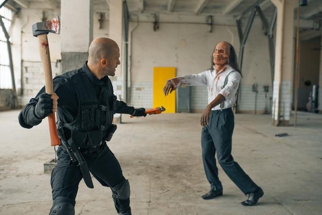 Militaire man met bijl, strijd met zombie in verlaten fabriek. horror in de stad, griezelige beestjes, doomsday apocalyps, bloedige kwaadaardige monsters