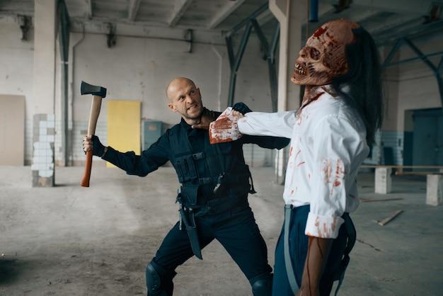 Militaire man met bijl, strijd met zombie in verlaten fabriek. horror in de stad, griezelige beestjes, doomsday apocalyps