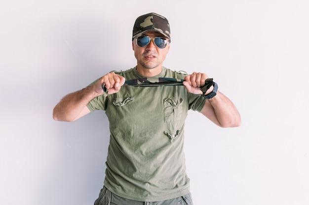 Militaire man met camouflage pet en zonnebril, geklemd een camouflage sjaal, op een witte muur
