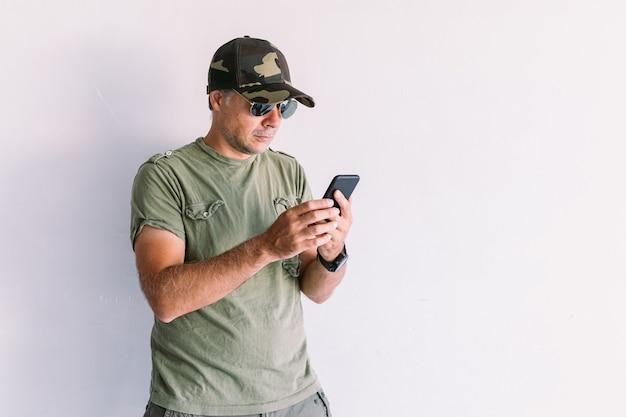 Militaire man met camouflage pet en zonnebril, kijkend naar mobiele telefoon, op een witte muur