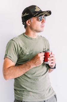 Militaire man met camouflage pet en zonnebril, met een kopje koffie, op een witte muur