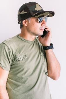 Militaire man met camouflage pet en zonnebril, praten aan de telefoon, op een witte muur