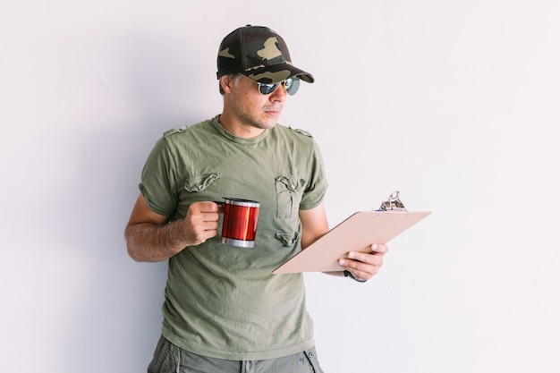 Militaire man met camouflage pet en zonnebril, schrijven in een rapport in een map, een kopje koffie drinken, op een witte muur