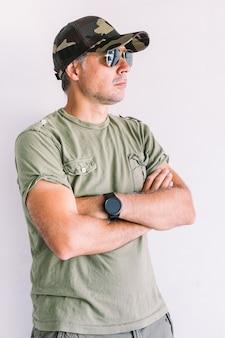 Militaire man met camouflagepet en zonnebril, gekruiste armen, op een witte muur
