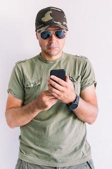 Militaire man met camouflagepet en zonnebril, kijkend naar zijn smartphone, op een witte muur