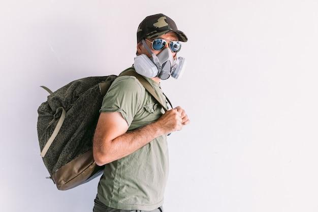 Militaire man met camouflagepet en zonnebril, met beschermingsmasker en militaire rugzak, op een witte muur