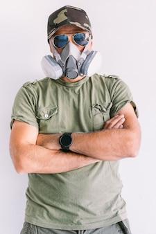 Militaire man met camouflagepet en zonnebril, met beschermingsmasker, op een witte muur