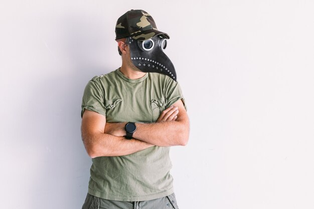 Militaire man met camouflagepet en zonnebril, met builenpestmasker, op een witte muur