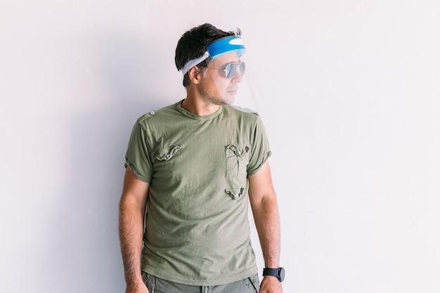 Militaire man met camouflagepet en zonnebril, met een beschermend antivirusscherm, op een witte muur