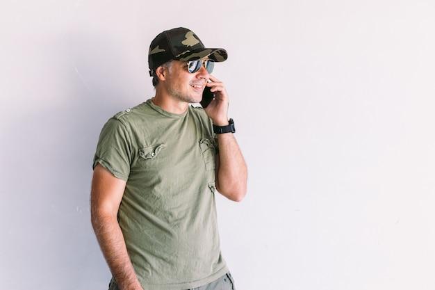 Militaire man met camouflagepet en zonnebril, pratend op de mobiele telefoon, op een witte muur